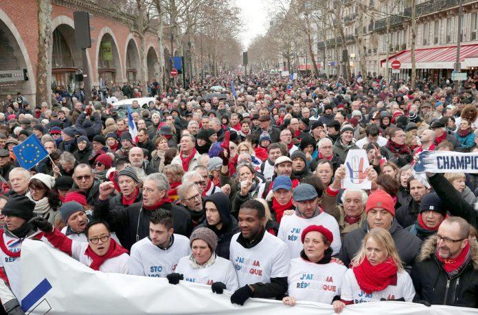 پیرس: زرد جیکٹ تحریک کے مخالفین سرخ اسکارف گلے میں ڈال کر احتجاجی ریلی نکال رہے ہیں