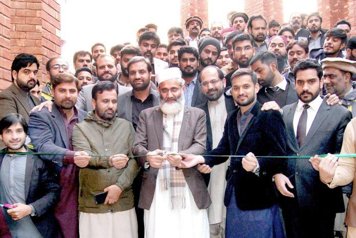 لاہور:امیر جماعت اسلامی سراج الحق تصویری نمائش کا ربن کاٹ کر افتتاح کررہے ہیں
