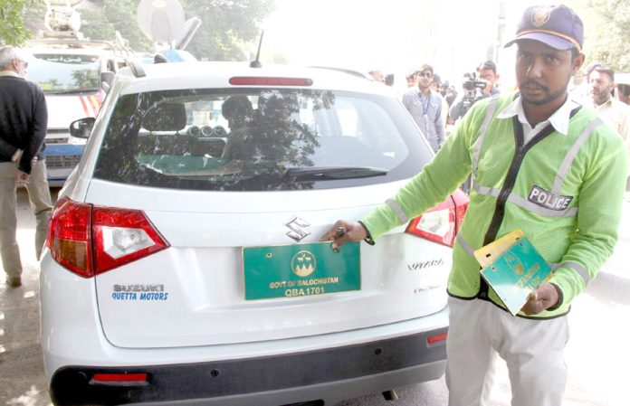 شارع فیصل پر ٹریفک پولیس کا اہلکار فینسی نمبر پلیٹ گاڑی کا چالان کر رہا ہے