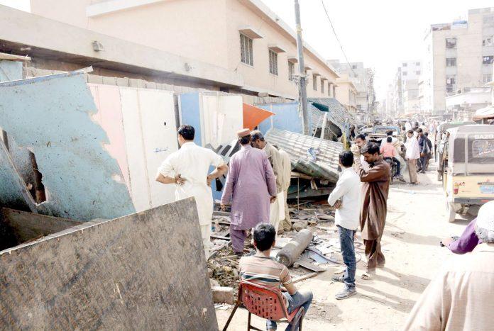 لیاقت آباد سپر مارکیٹ میں انسداد تجاوزات کی کارروائی کے بعد بکھرے ہوئے سامان کے قریب دکاندار کھڑے ہوئے ہیں