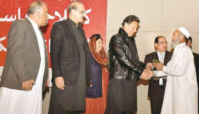 اسلام آباد: وزیراعظم عمران خان صحت کارڈ اجرا کے موقع پر ایک شہری کو کارڈ دے رہے ہیں