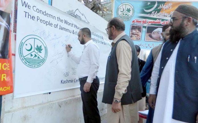 کراچی:ایک شخص کشمیریوں سے یکجہتی کے لیے بینرپر دستخط کررہا ہے