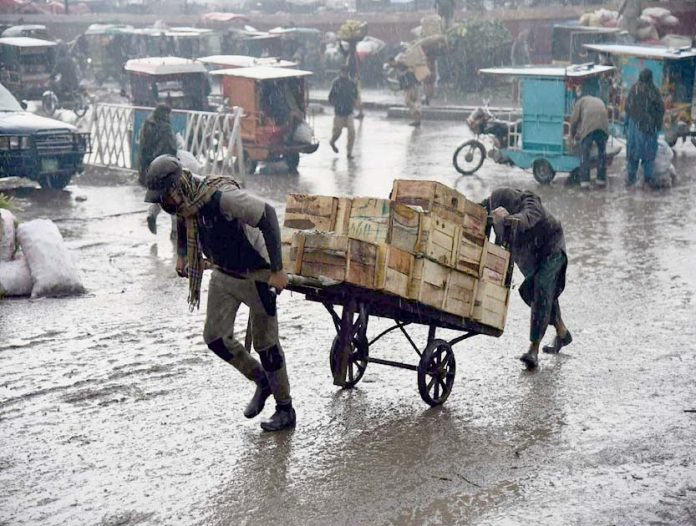 لاہور،موسلادھاربارش کے دوران ریڑھی بان سامان لے کر جارہے ہیں