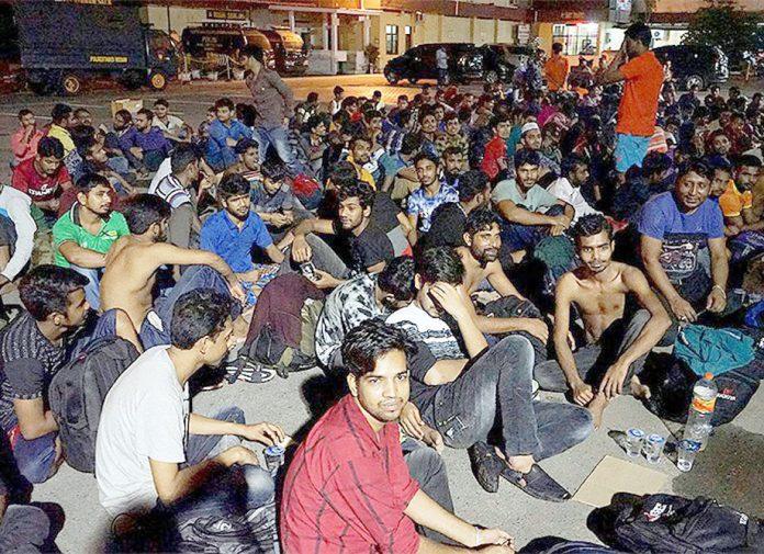 جکارتا: دکانوں میں قید بنگلادیشی باشندے بازیاب ہونے کے بعد پولیس اسٹیشن کے باہر بیٹھے ہیں