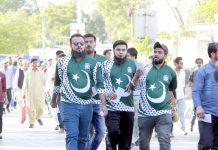 قومی پرچم والی شرٹ زیب تن کیے ہوئے چند نوجوان نیشنل اسٹیڈیم میں داخل ہوتے ہوئے