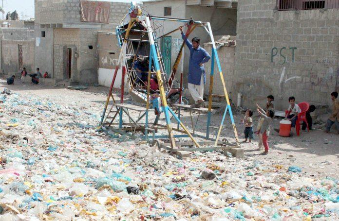 ابراہیم حیدری میں رہائشی گھروں کے سامنے کچرے کے ڈھیر میں بچے کھیل رہے ہیں