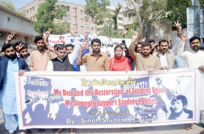 حیدر آباد: سندھ اسٹوڈنٹس کونسل کے تحت طلبہ یونین کی بحالی کے لیے مظاہرے کے شرکا بینر اٹھائے ہوئے ہیں