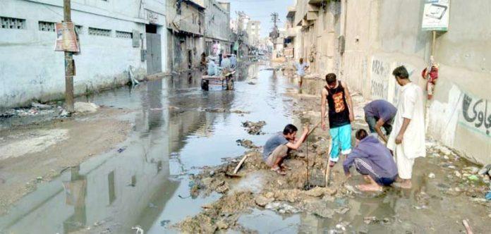 شیرشاہ اردو بازار میں گٹر اُبلنے کی وجہ سے سڑک تالاب بنی ہوئی ہے، رہائشی اپنی مدد آپ کے تحت گٹر کھولنے کی کوشش کر رہے ہیں