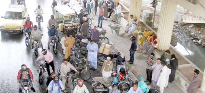 راشد منہاس روڈ پر موٹر سائیکل سوار بارش سے بچنے کیلیے پل کے نیچے جمع ہیں