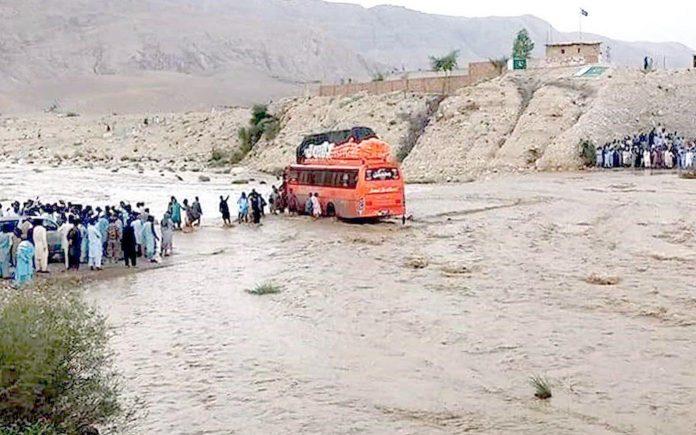 کوئٹہ: بارش کے باعث ندی میں سیلاب میں پھنسی ہوئی بس سے مسافروں کو نکالا جارہا ہے