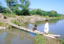چنیوٹ،بچے نہر پر بنے عارضی پل پر سے گزررہے ہیں جو کسی بھی حادثے کا باعث بن سکتا ہے