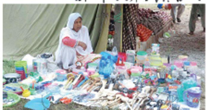 ایک خاتون گھریلو استعمال کی اشیاء فروخت کرنے کے لیے اسٹال لگائے بیٹھی ہیں