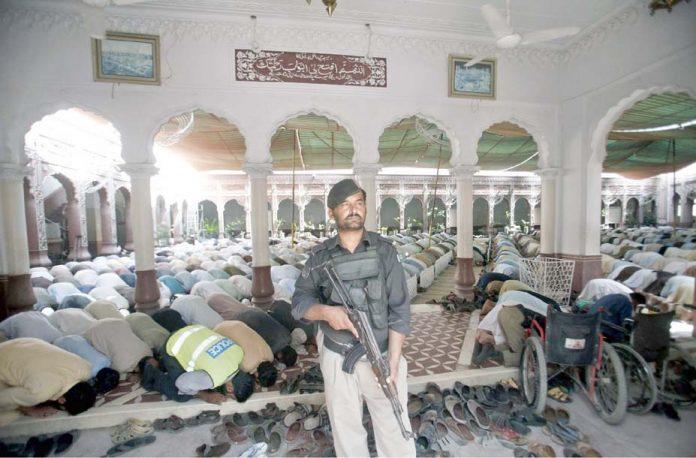 پشاور،پولیس اہلکار نماز جمعہ کے دوران چوکس کھڑا ہے