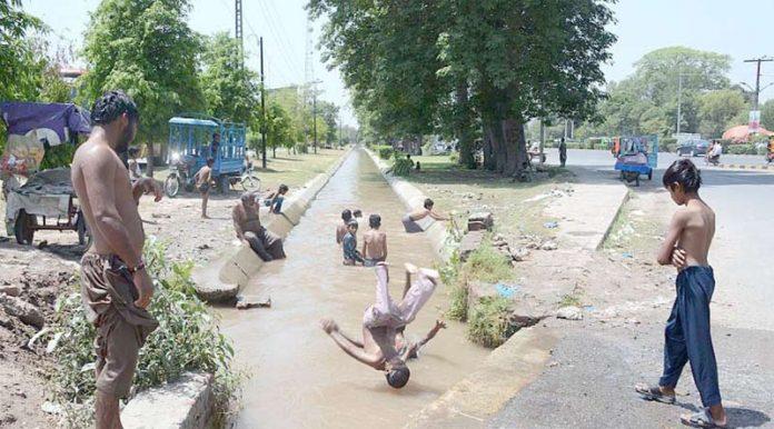 فیصل آباد ،گرمی کے ستائے ہوئے منچلے مقامی نہر میں نہارہے ہیں