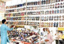 حیدر آباد : باچا خان چوک پر دکاندار گاہک کو متوجہ کرنے کے لیے جوتوں کو ترتیب سے رکھ رہا ہے