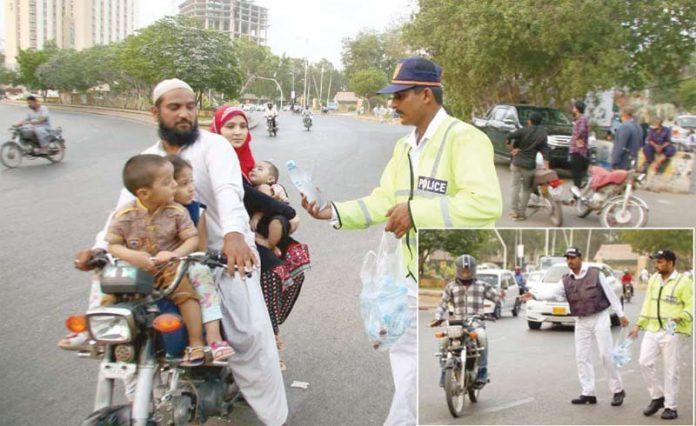 کراچی: ٹریفک اہلکار افطار سے قبل مسافروں کو پانی کی بوتلیں دے رہے ہیں