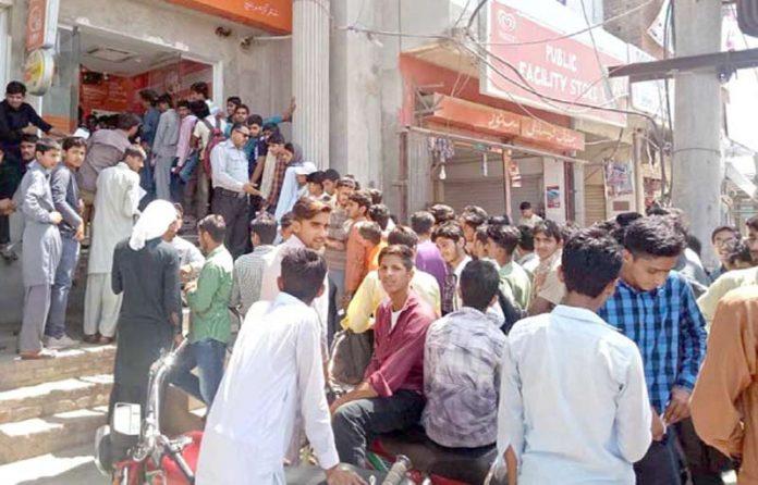 سیالکوٹ: شہریوں کی بڑی تعداد نئے نوٹوں کے حصول کے لیے بینک کے باہر کھڑی ہے