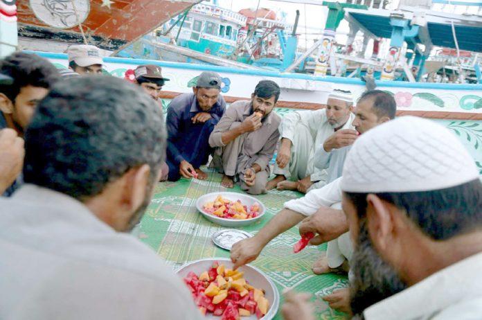 ساحلی علاقے میں ماہی گیر برادری سے تعلق رکھنے والے افراد روزہ افطار کررہے ہیں