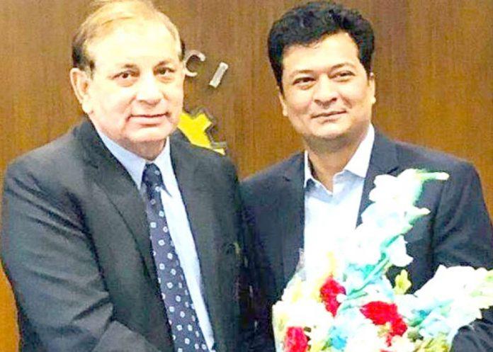 نکاٹی کے سابق صدر شاہد صابر ایف پی سی سی آئی کے قائم مقام صدر نور احمد خان کو گلدستہ پیش کررہے ہیں