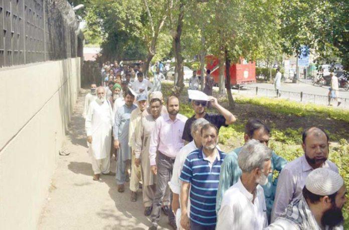 لاہور: اسٹیٹ بینک کی جانب سے پابندی کے بعد لوگ پرائز بانڈ کیش کرانے کے لیے بینک کے باہر قطار میں کھڑے ہیں