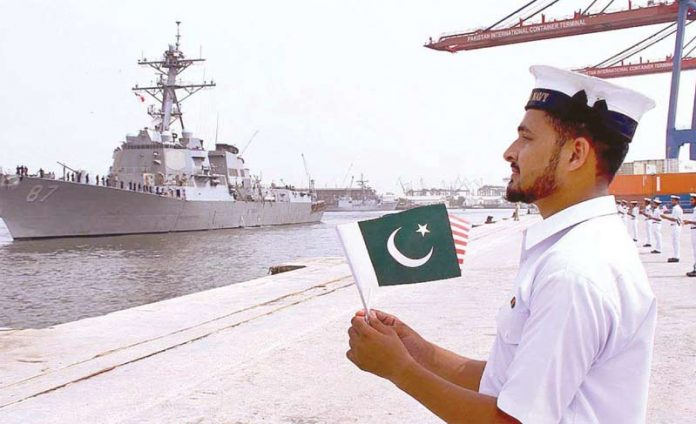 کراچی: امریکی بحری بیڑے کی کراچی آمد پر پاکستانی پرچم اٹھائے نیوی اہلکار استقبال کررہا ہے