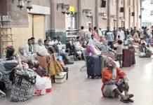لاہور،ریلوے اسٹیشن میں بیٹھے مسافر اپنی مطلوبہ ٹرین کے آنے کا انتظار کررہے ہیں