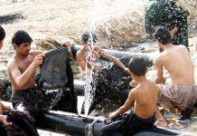 لیاری ندی سے گزرنے والی پائپ لائن سے رسنے والے پانی سے نوجوان لطف اندوز ہو رہے ہیں