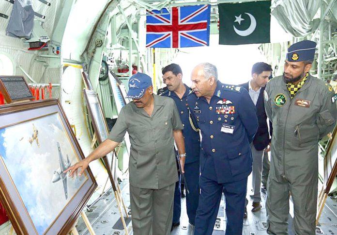 سربراہ پاک فضائیہ مجاہد انور خان کو رائل انٹرنیشنل ائر ٹیٹو شو میں ہرکولیس سی130کے معائنے کے دوران پینٹنگ دکھائی جارہی ہے