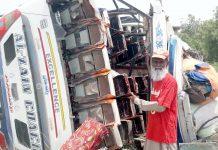 حیدرآباد: ٹائر پھٹ جانے کے باعث حادثے کا شکار ہونے والی بس کے قریب رضا کار کھڑا ہے