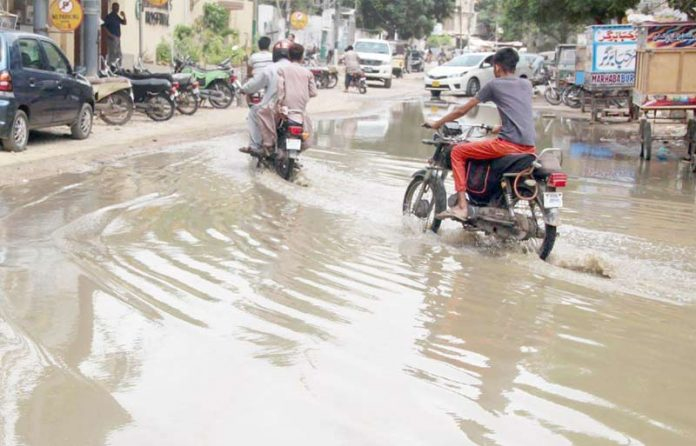 لائنز ایریا کے علاقے میں ٹوٹی ہوئی سڑک پر جمع پانی سے موٹر سائیکل سوار گزر رہے ہیں