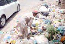 حیدر آباد : سڑک کنارے پڑے کچرے کے ڈھیر سے ایک شخص اپنے کام کی چیزیں تلاش کررہا ہے