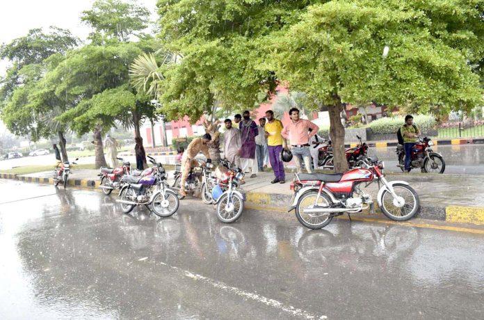 فیصل آباد : تیز بارش کے باعث موٹر سائیکل سوار سڑک کنارے درخت کے نیچے کھڑے ہیں