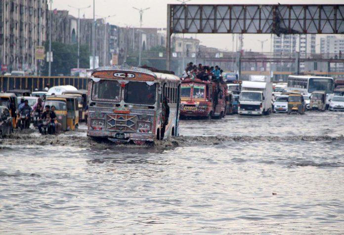 کراچی: ناگن چورنگی پر بارش کے بعد جمع ہونے والے پانی سے گاڑیاں گزر ہی ہیں
