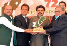 صوبائی وزیر ناصر حسین شاہ اور کمشنر کراچی افتخار شلوانی معروف تاجر سراج تیلی کو لائف ٹائم اچیومنٹ ایوارڈ دے رہے ہیں