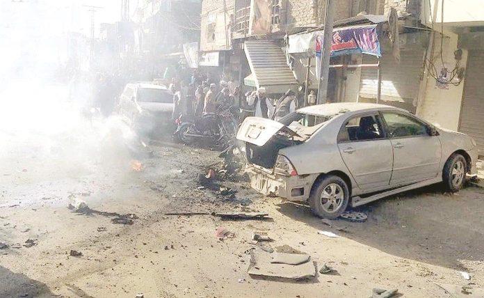 کوئٹہ: چمن روڈ پر ہونیوالے دھماکے کے بعد جائے وقوع پر تباہ شدہ کار کے قریب لوگ جمع ہیں
