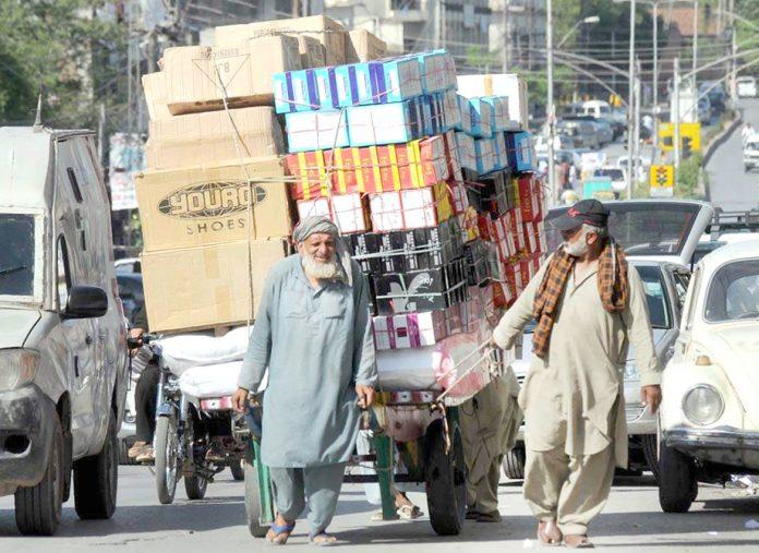 معمر مزدور بھاری بھرکم سامان دکانوں پر سپلائی کرنے کے لیے ہاتھوں کے ذریعے کھینچ کرلے جارہا ہے