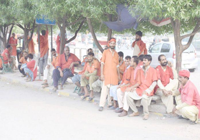 لاہور،ریلوے اسٹیشن کے باہر قلی سخت گرمی میں مسافروں کا انتظار کررہے ہیں