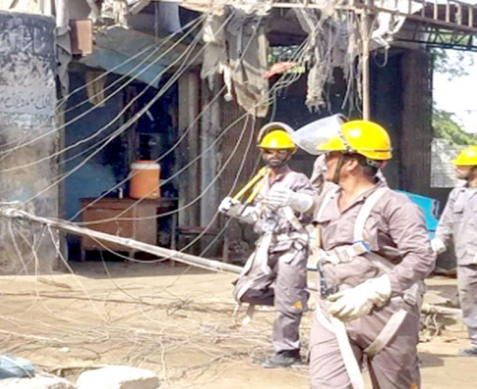 کراچی: کے الیکٹرک کا عملہ بجلی کے پول پر لگی غیر قانونی کیبل ہٹا رہا ہے