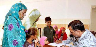 کراچی: مبارک ویلیج میں پاکستان نیوی کے آنکھوں کے مفت علاج کے کیمپ میں خاتون چیک اپ کروا رہی ہے