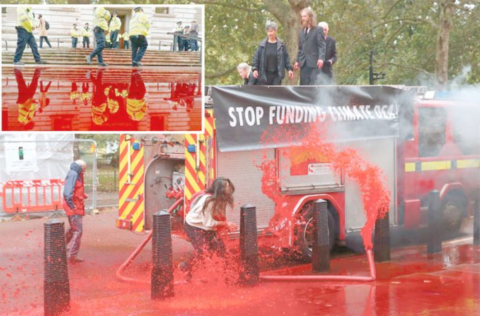لندن: ماحول دوست سماجی کارکن وزراتِ خزانہ کی عمارت کے باہر مصنوعی خون بہا رہے ہیں